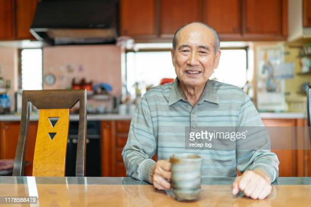 portrait of happy senior man at home - japanese old man stock pictures, royalty-free photos & images
