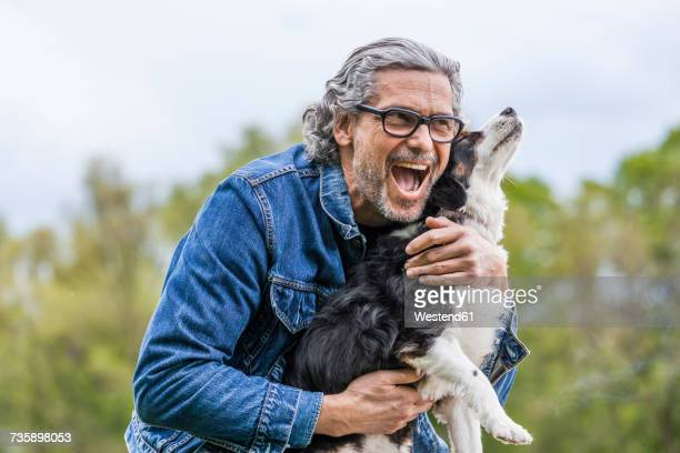 portrait of happy senior man cuddling his dog - young at heart stock pictures, royalty-free photos & images