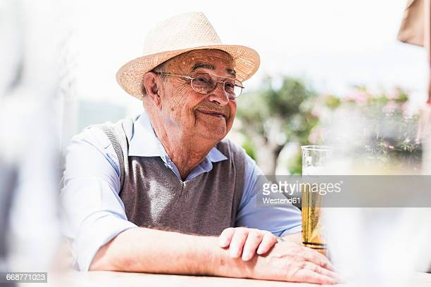 Portrait of happy senior man drinking glass of beer in a sidewalk cafe