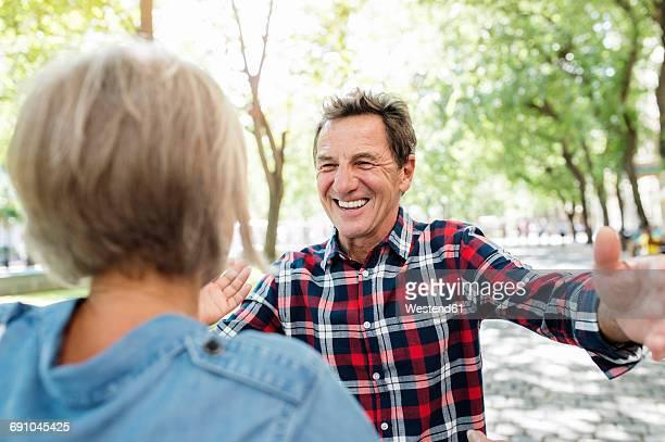 Portrait of happy senior man greeting senior woman