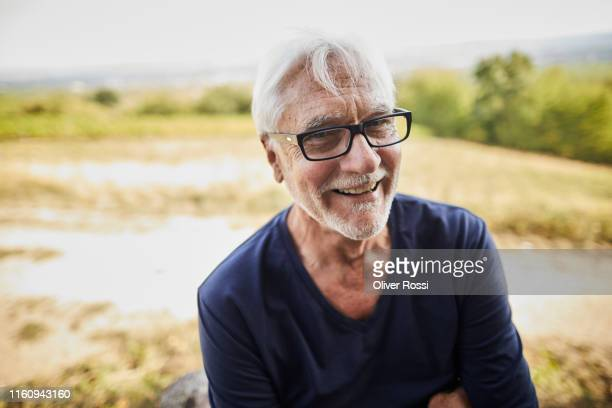 portrait of happy senior man in the countryside - 65 69 jahre stock-fotos und bilder