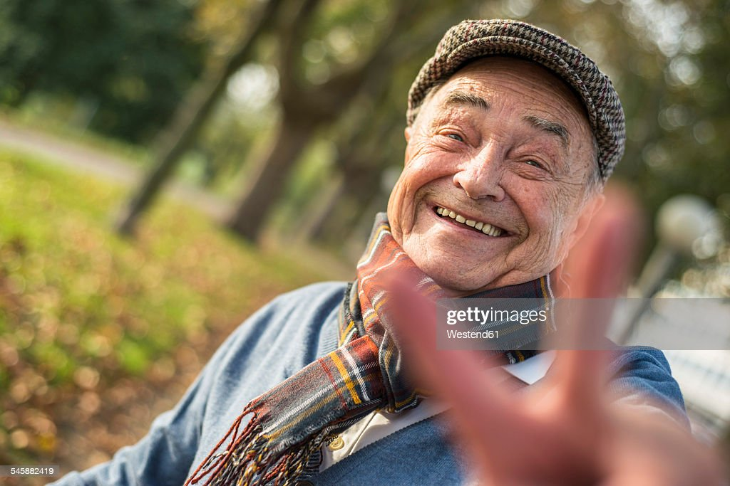 Portrait of happy senior man outdoors doing victory sign : Stock Photo