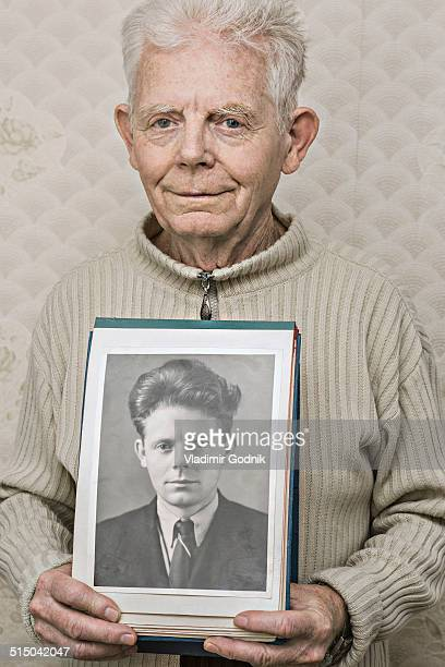 Portrait of happy senior man showing picture of himself in his twenties