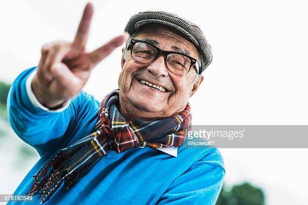 Portrait of happy senior man showing victory sign