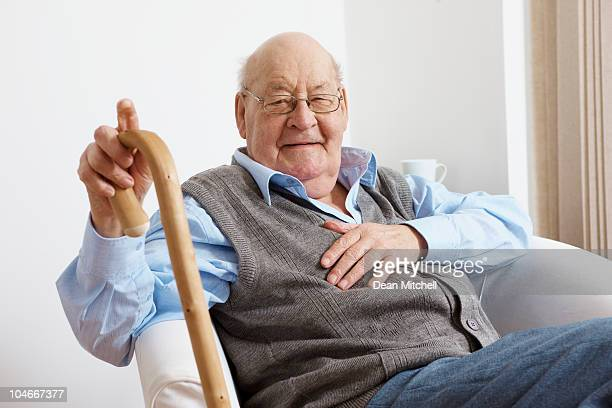 portrait of happy senior man sitting in chair - walking cane stock photos and pictures