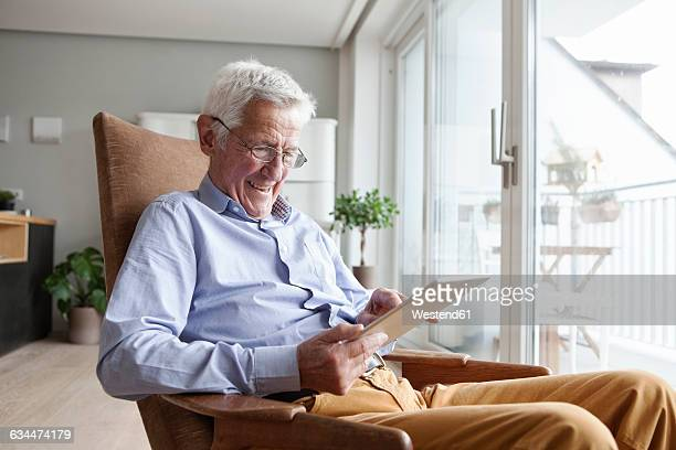 Portrait of happy senior man sitting on armchair at home using digital tablet
