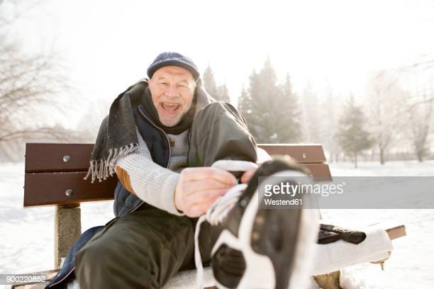 portrait of happy senior man sitting on bench in winter landscape putting on ice skates - joy stock pictures, royalty-free photos & images