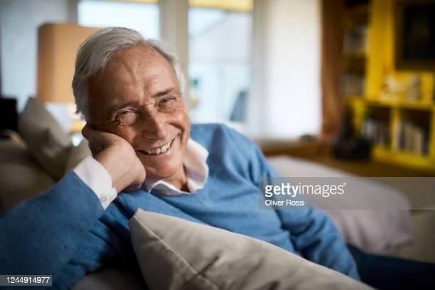 portrait of happy senior man sitting on couch at home - disruptaging stock-fotos und bilder
