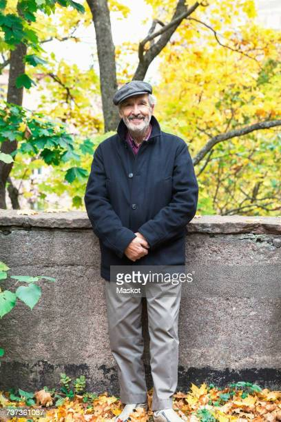 Portrait of happy senior man standing with hands clasped in park during autumn