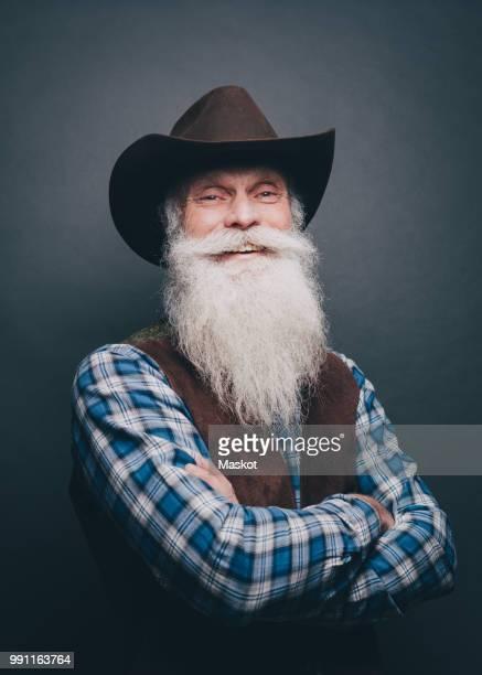 portrait of happy senior man wearing cowboy hat against gray background - vaqueros fotografías e imágenes de stock