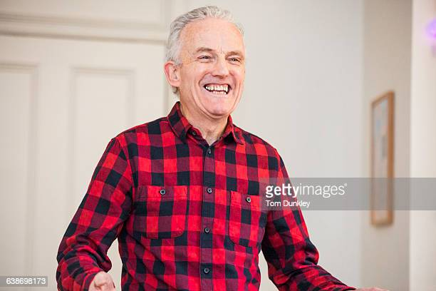 Portrait of happy senior man wearing red checked shirt