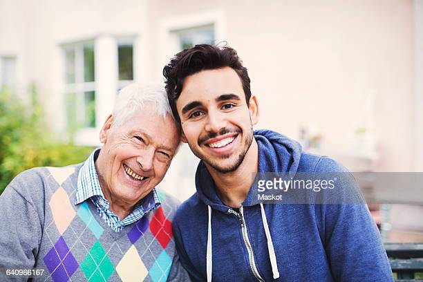Portrait of happy senior man with caretaker sitting outdoors
