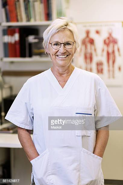 Portrait of happy senior orthopedic surgeon standing with hands in pockets in clinic