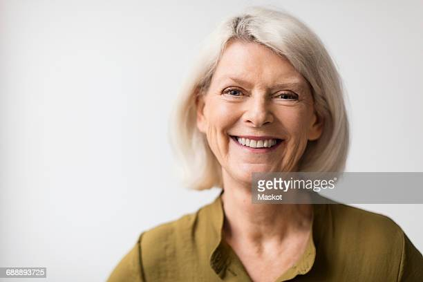 Portrait of happy senior woman against white background
