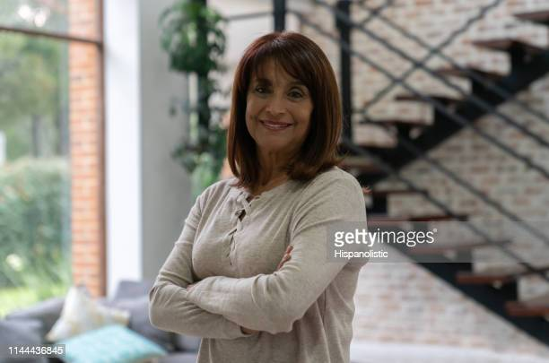 portrait of happy senior woman at home facing camera with arms crossed - hispanolistic stock photos and pictures