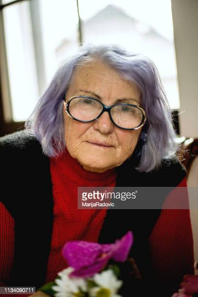 portrait of happy senior woman at home - purple hair stock photos and pictures