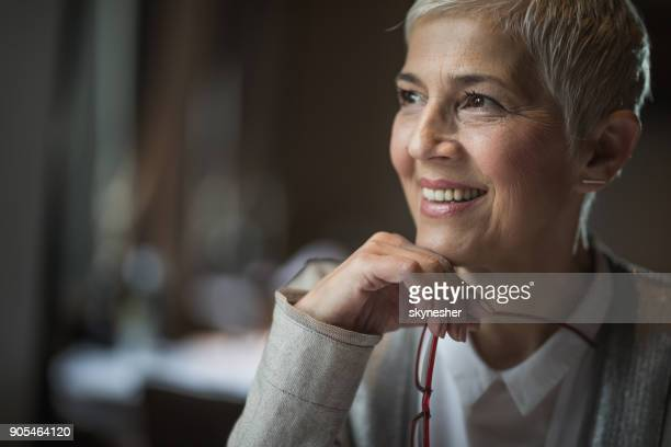 portrait of happy senior woman day dreaming about something. - introspection stock pictures, royalty-free photos & images
