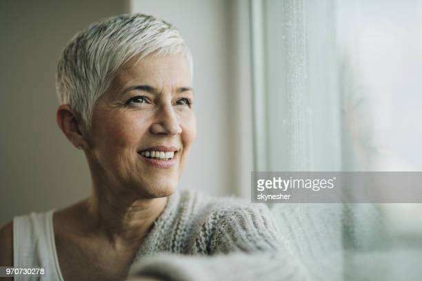 portrait of happy senior woman day dreaming by the window. - candid stock pictures, royalty-free photos & images