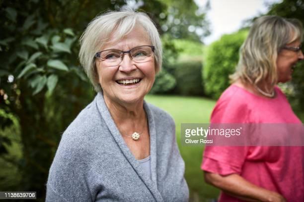 portrait of happy senior woman in garden - frau 65 jahre stock-fotos und bilder