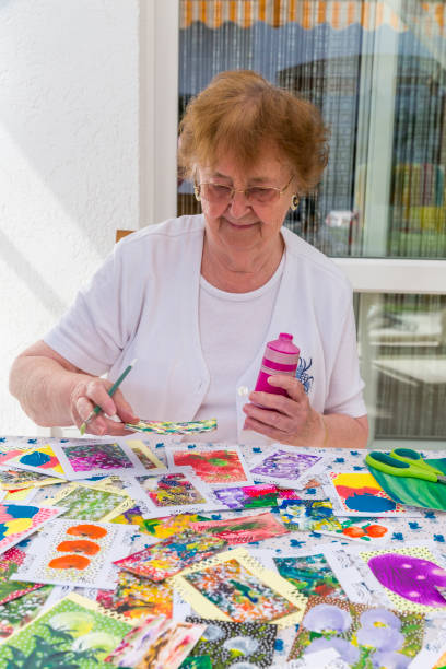 Portrait of happy senior woman painting on terrace