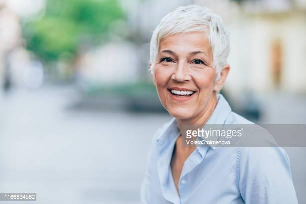 porträt einer glücklichen seniorin - arbeitende rentner stock-fotos und bilder