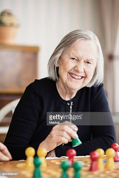 Portrait of happy senior woman playing Ludo in nursing home