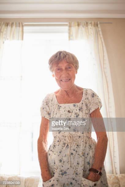 portrait of happy senior woman sanding at brightly lit home - eine seniorin allein stock-fotos und bilder