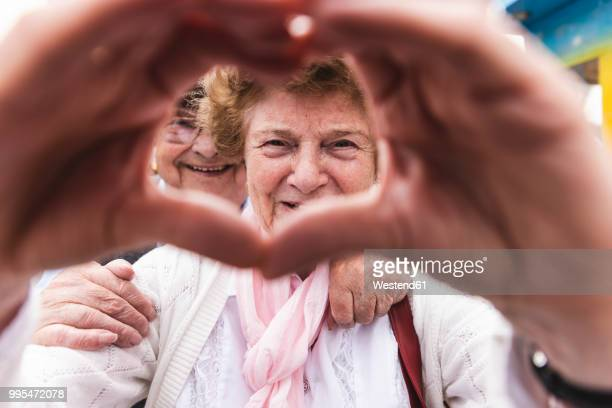 portrait of happy senior woman shaping heart with her hands - tradition stock-fotos und bilder