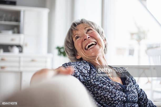 Portrait of happy senior woman sitting on couch at home