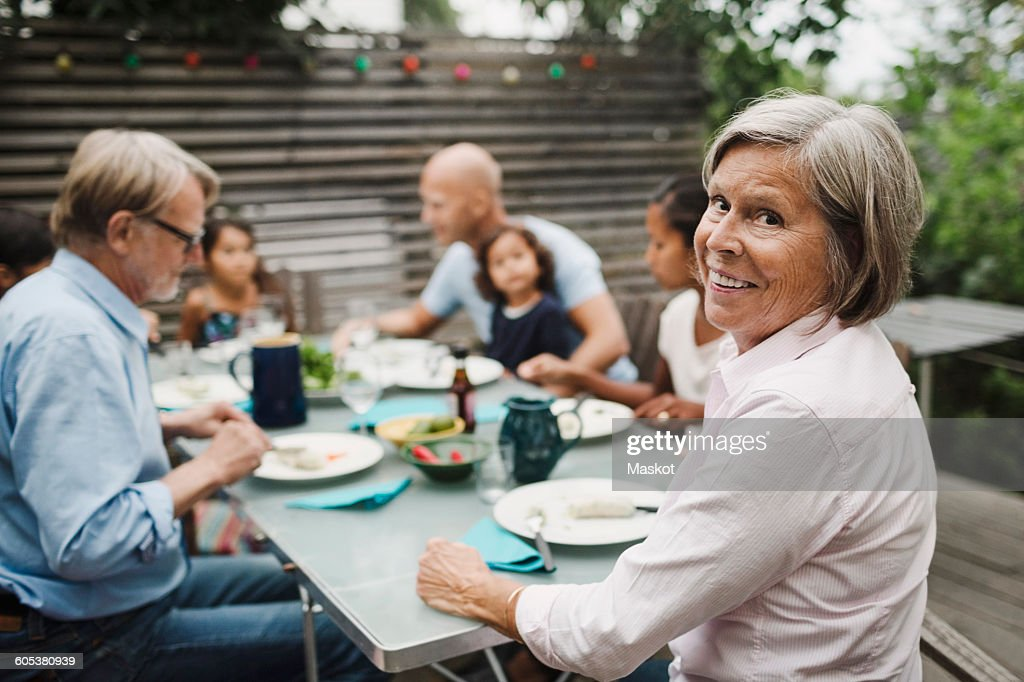 Portrait of happy senior woman sitting with family at outdoor dining table : Stock Photo