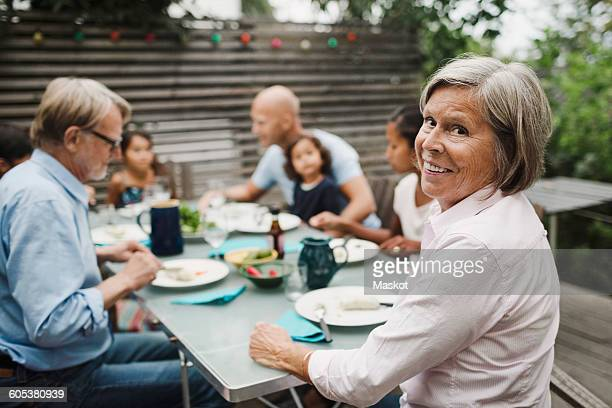 portrait of happy senior woman sitting with family at outdoor dining table - mother in law stock pictures, royalty-free photos & images