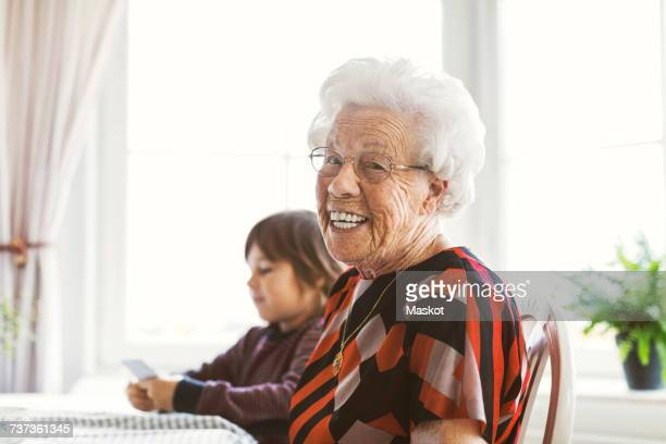 Portrait of happy senior woman sitting with great grandson playing cards at home