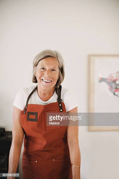 Portrait of happy senior woman wearing apron at home