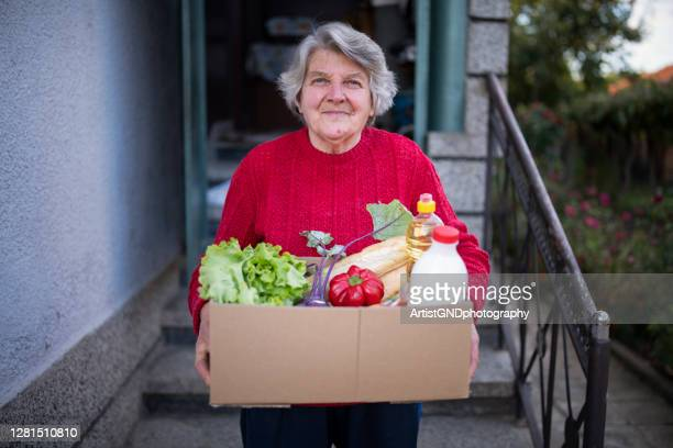portrait of happy senior woman with received crate with food during pandemic. - charity and relief work stock pictures, royalty-free photos & images