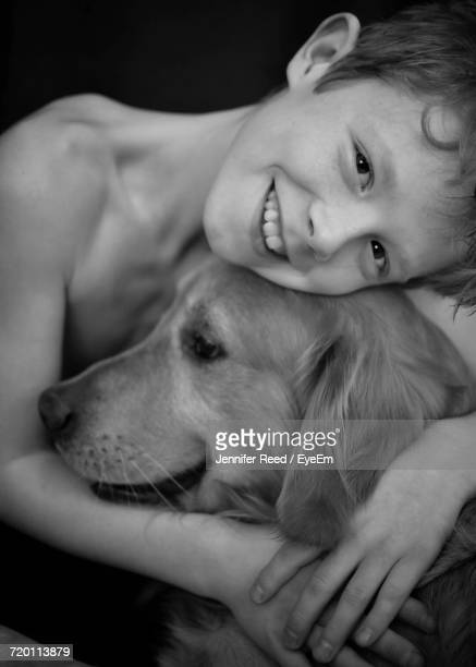 Portrait Of Happy Shirtless Boy Embracing Golden Retriever