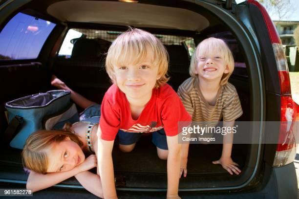 Portrait of happy siblings in car trunk