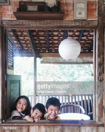 Portrait Of Happy Siblings Looking Through Window From House On Sunny Day