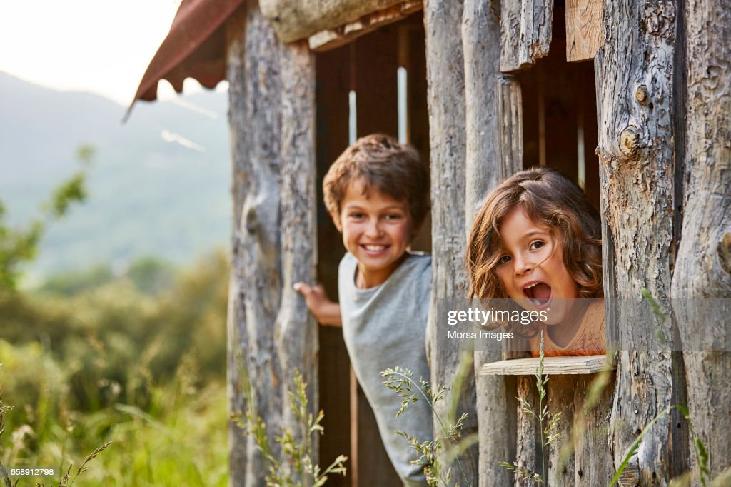 Portrait of happy siblings playing in log cabin : Stock Photo