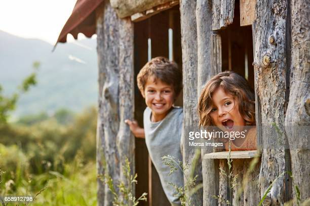 Portrait of happy siblings playing in log cabin