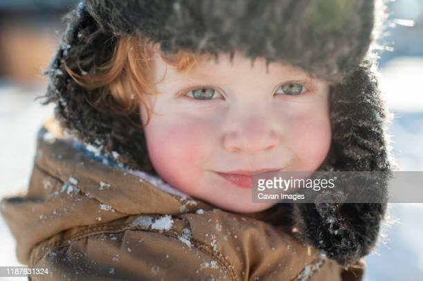 portrait of happy smiling toddler bundled up in winter hat in jacket - ピンクの頬 ストックフォトと画像