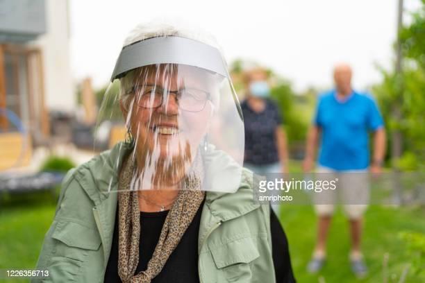 庭の顔の盾の後ろに幸せな笑顔の女性の肖像画 - フェイスシールド ストックフォトと画像
