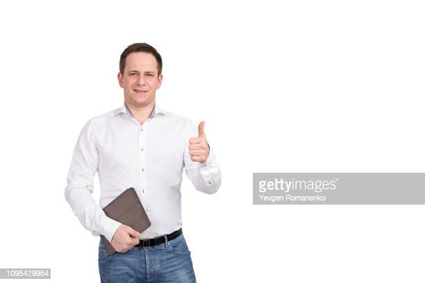 portrait of happy smiling young businessman with brown folder, shows thumb up sign on white background. - シャツ ストックフォトと画像