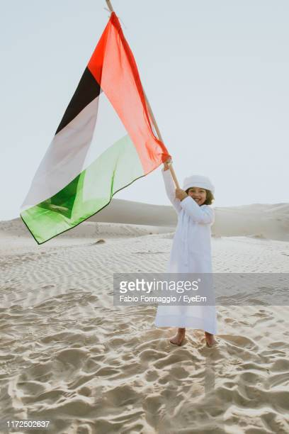 portrait of happy standing on united arab emirates flag at desert - united arab emirates flag stock photos and pictures