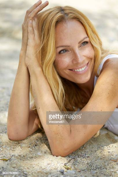 portrait of happy strawberry blonde woman lying on the beach - one mature woman only stock pictures, royalty-free photos & images