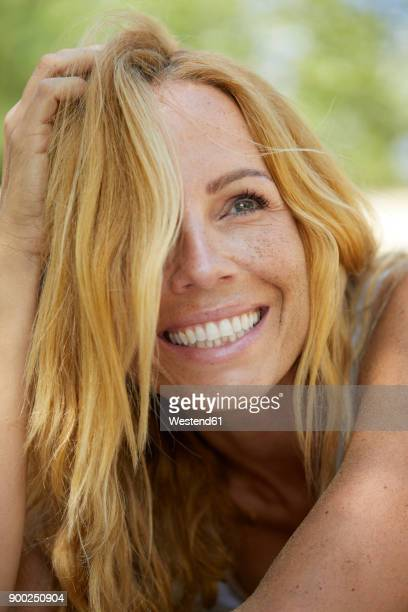Portrait of happy strawberry blonde woman with freckles