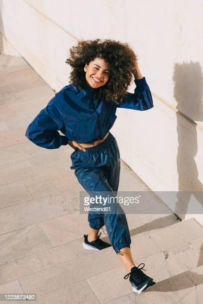 portrait of happy stylish young woman wearing tracksuit outdoors - trainingsanzug stock-fotos und bilder