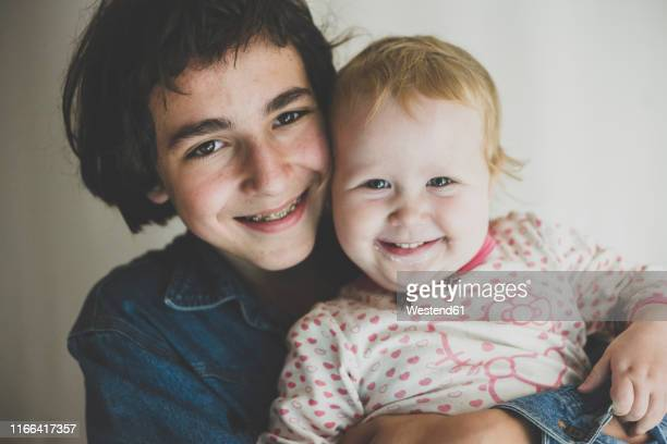 portrait of happy teenage boy hugging his toddler sister - 12 23 months stock pictures, royalty-free photos & images