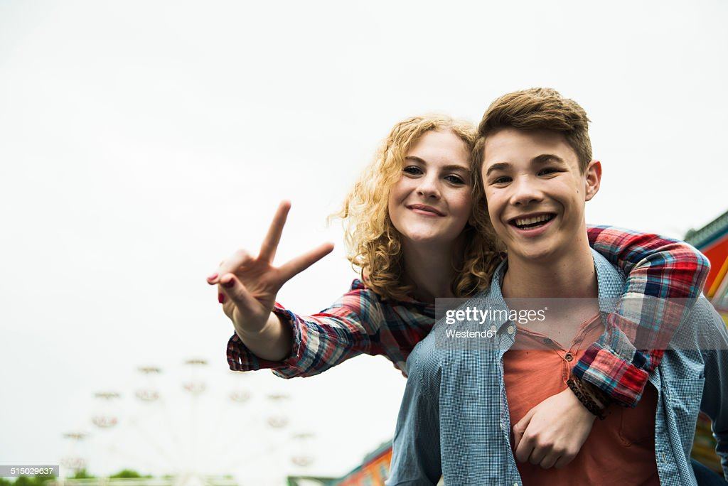 Portrait of happy teenage couple showing victory-sign : Stock-Foto