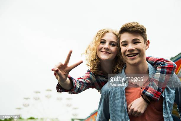 portrait of happy teenage couple showing victory-sign - jugendliche stock-fotos und bilder