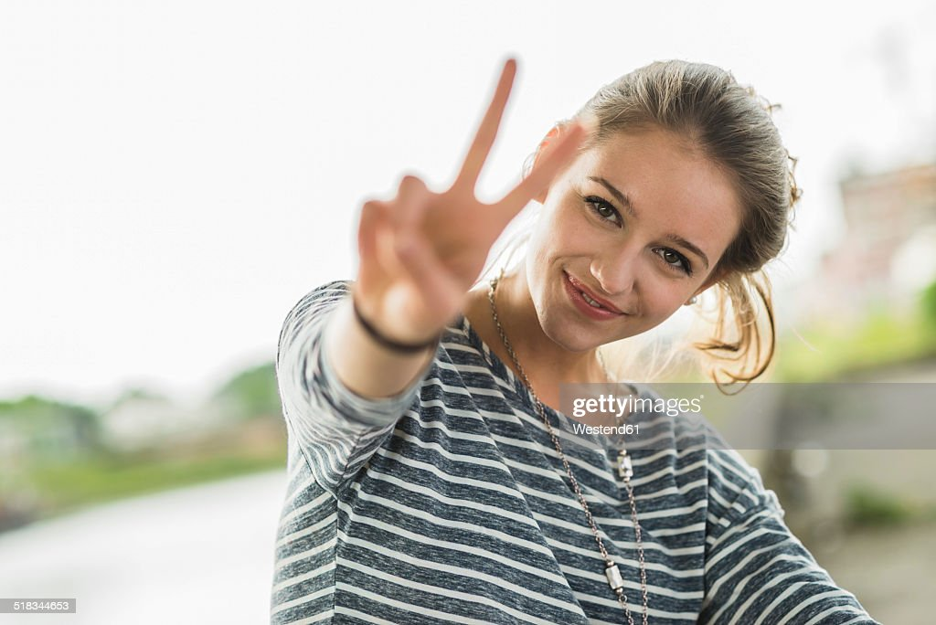 Portrait of happy teenage girl showing Victory sign : Stock-Foto